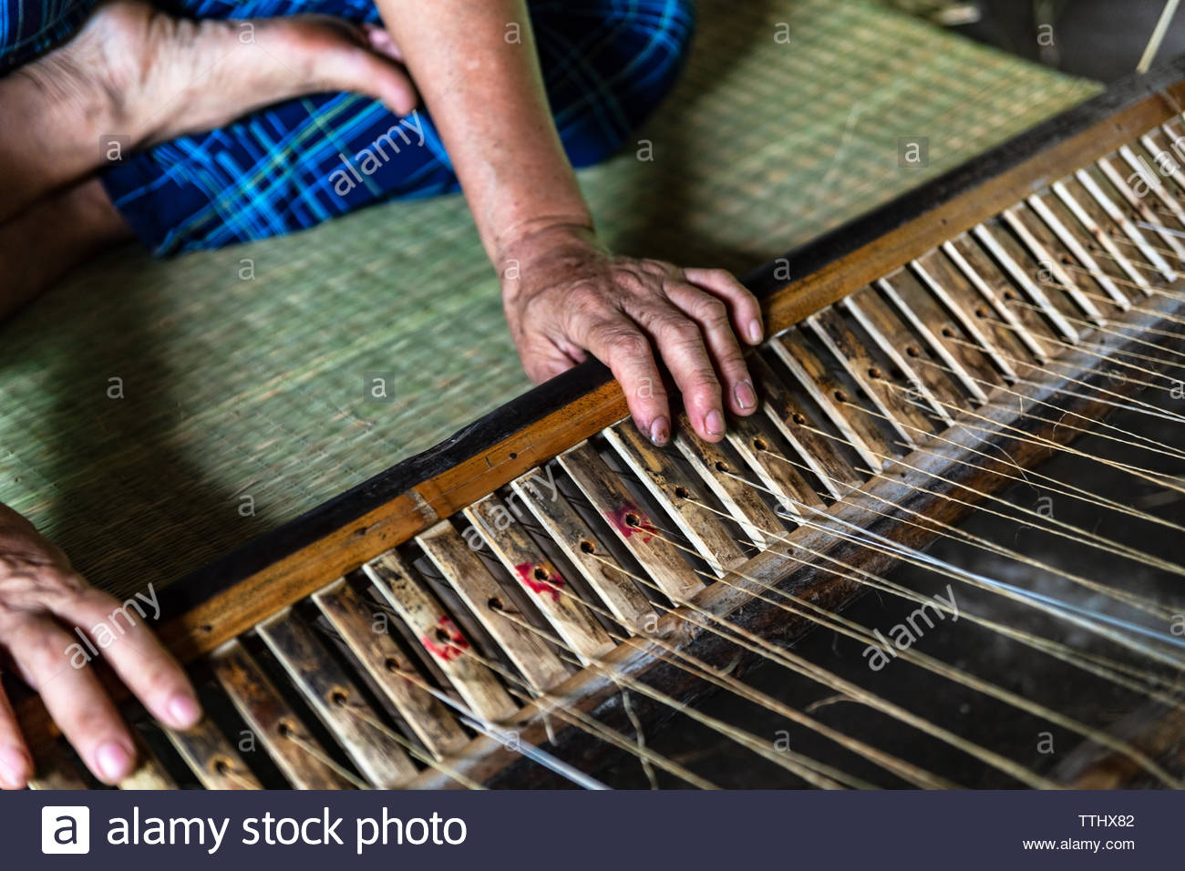 Close-up on the hands of an old woman weaving sedge mat in the small village of Ben Tre in the Mekong delta region, Vietnam - Stock Image