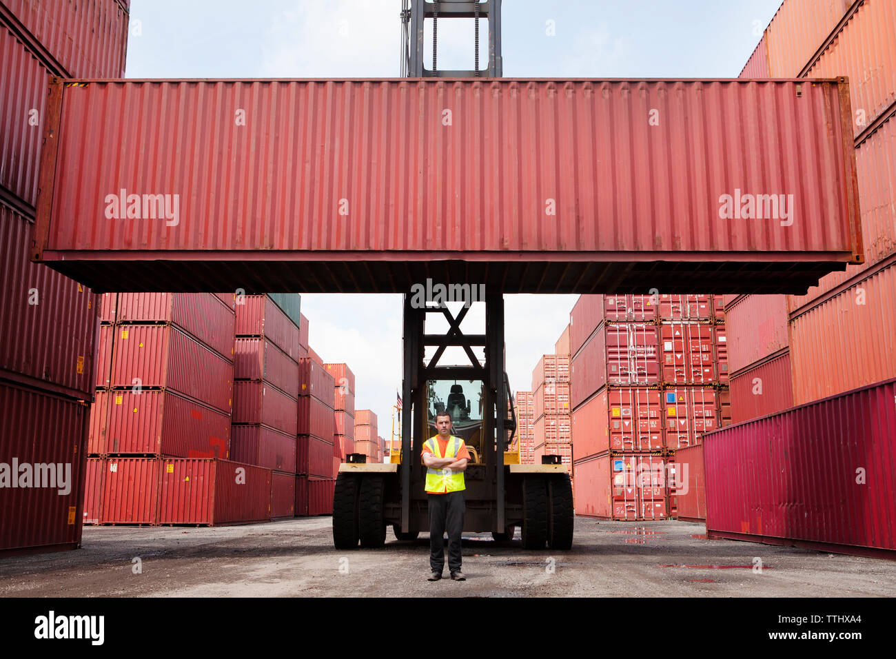 Man with arms crossed standing against forklift by cargo containers - Stock Image