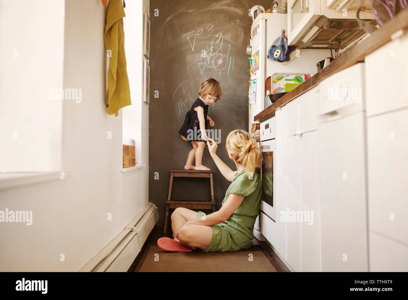 Mother giving chalk to daughter at home - Stock Image