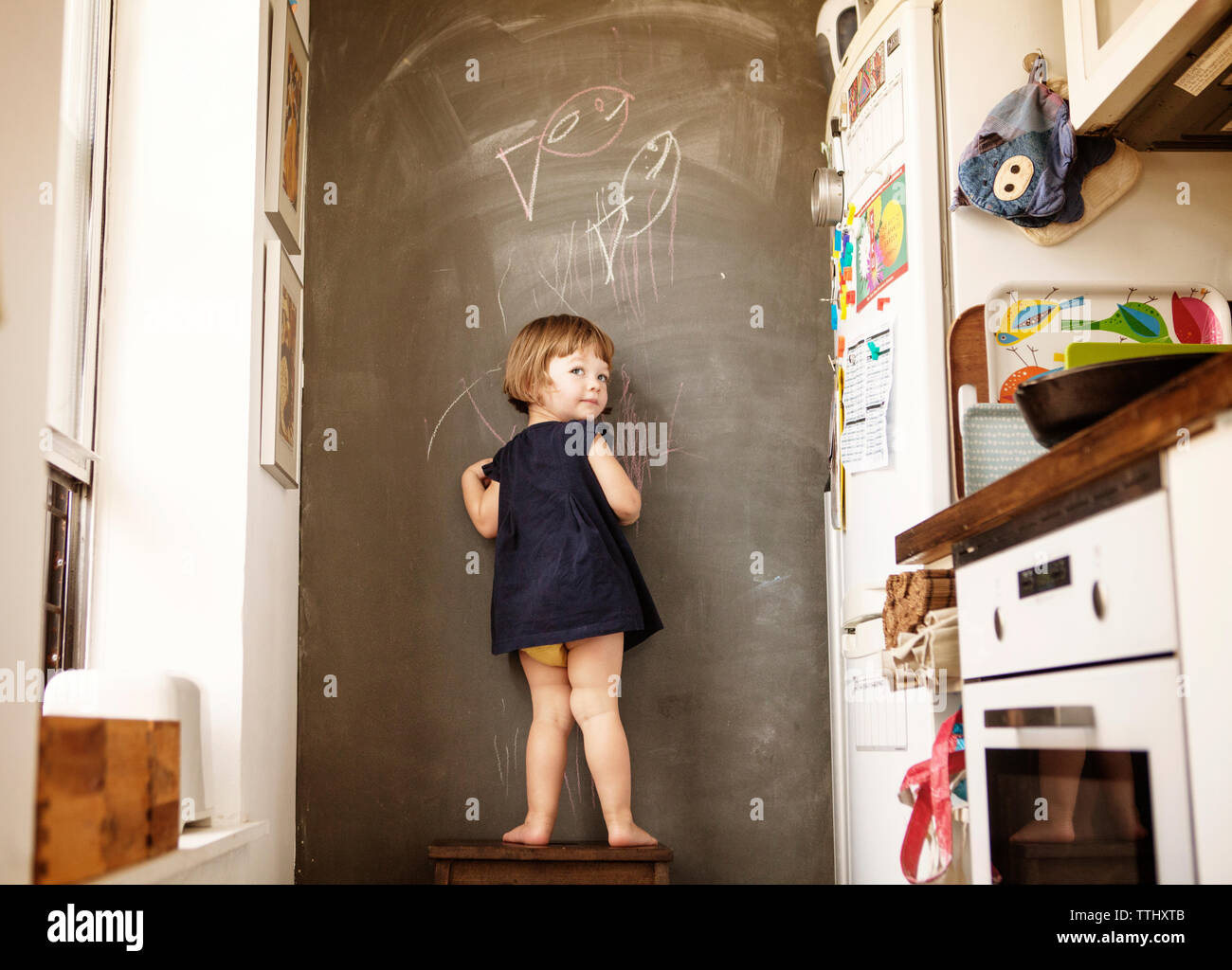 Rear view of girl writing on wall while standing on stool at home - Stock Image