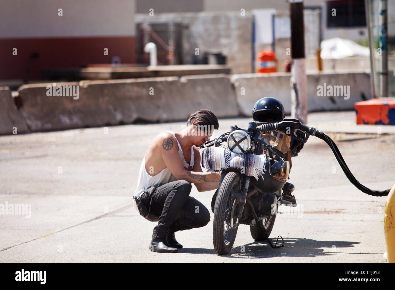 Side view of man refueling fuel in motorcycle at fuel pump - Stock Image