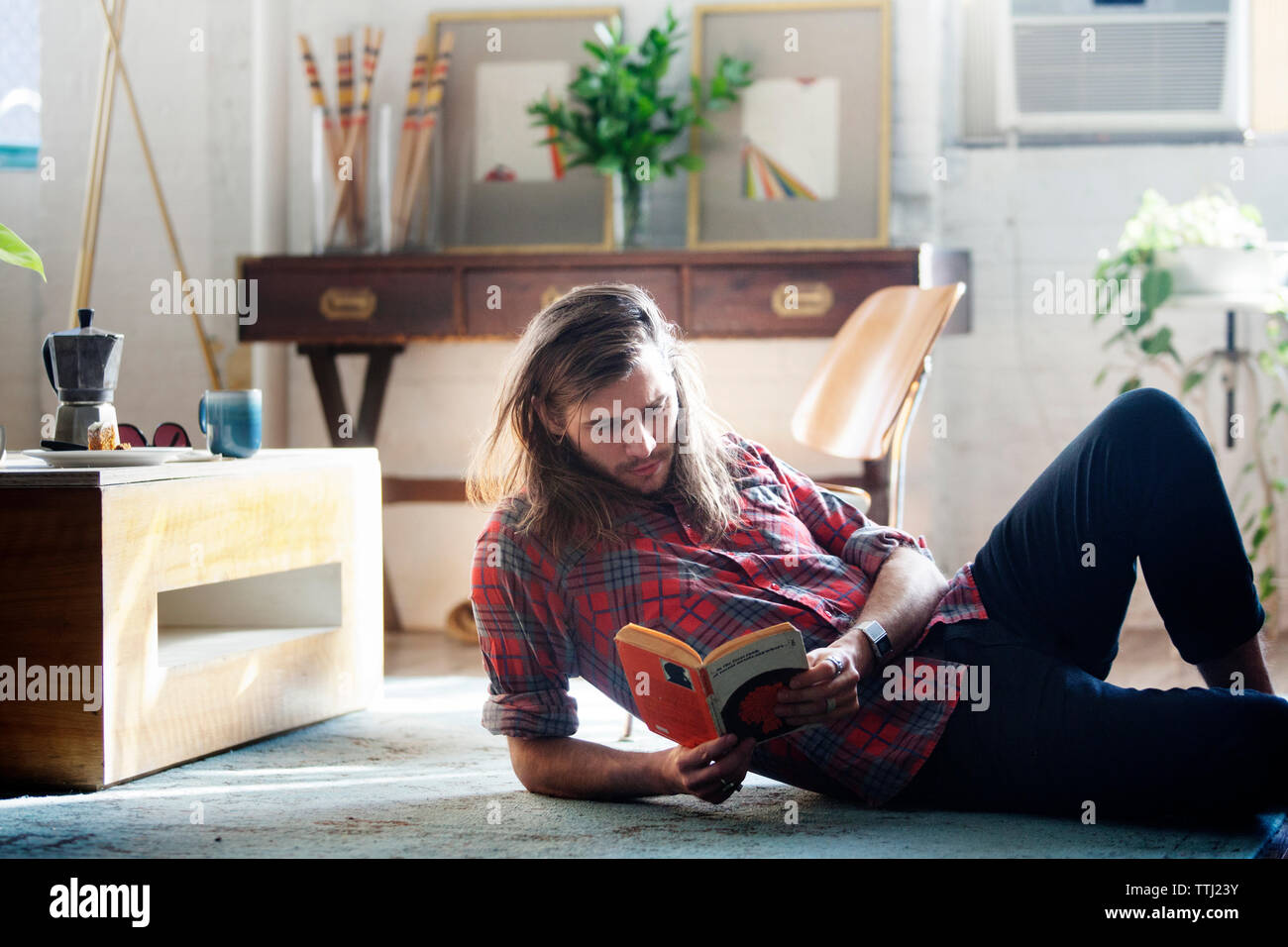 Man reading book while lying on floor at home - Stock Image