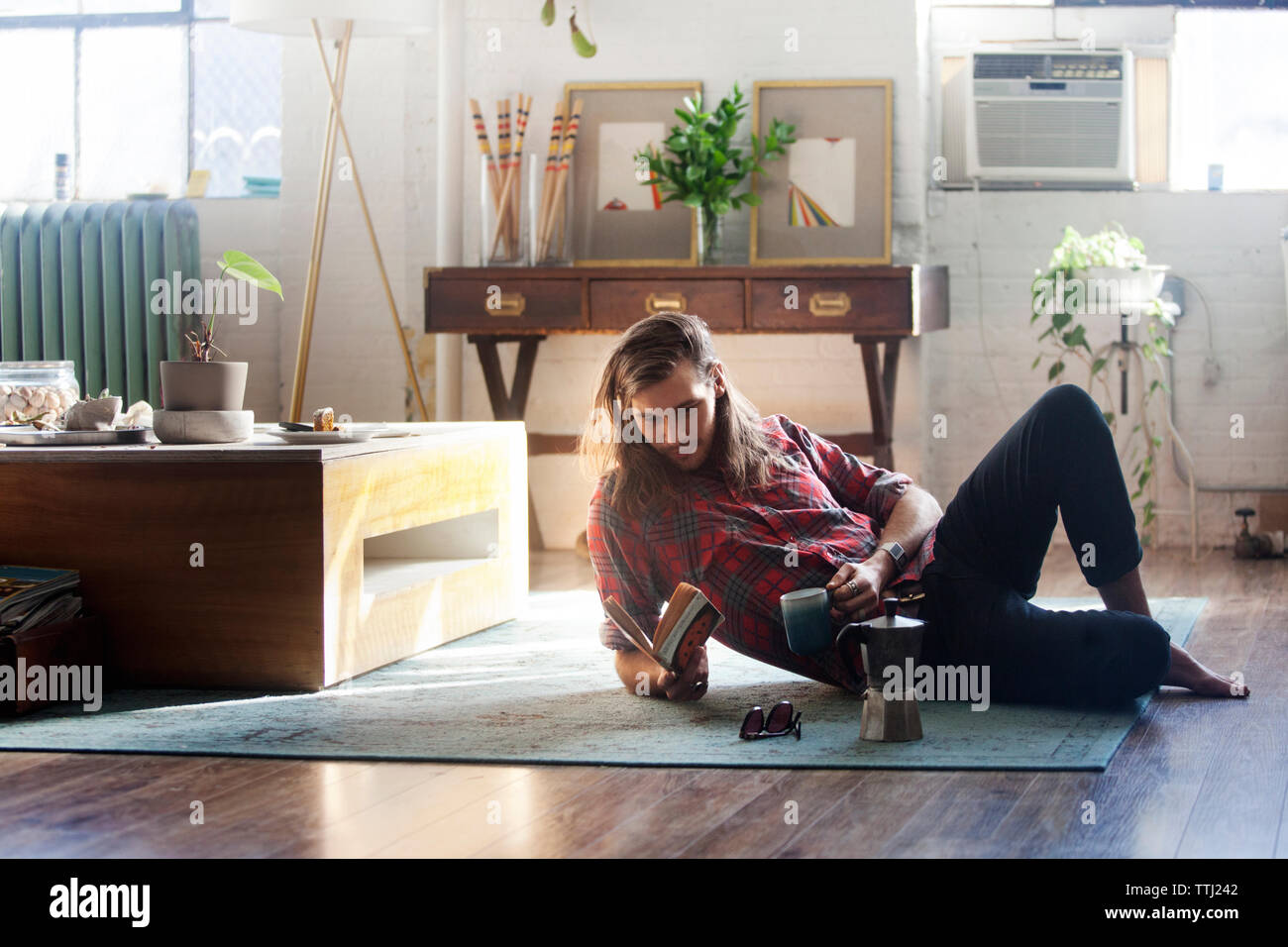 Man reading book while leaning on elbow at home - Stock Image