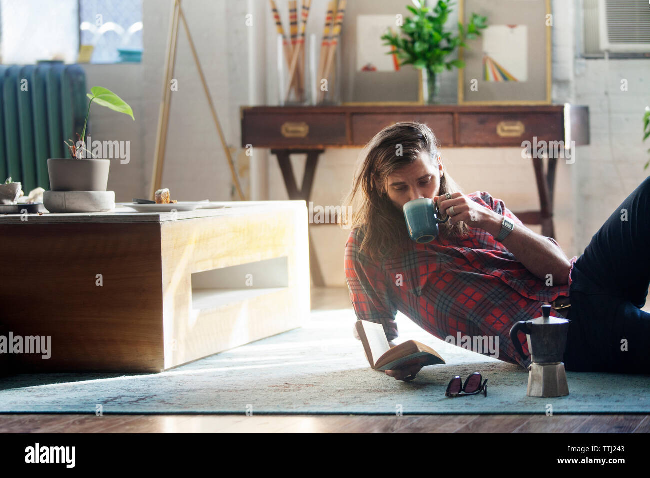 Man drinking coffee while reading book at home - Stock Image