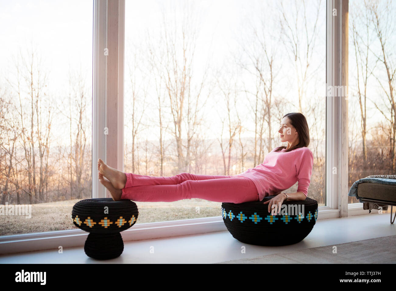 Side view of woman relaxing on ottomans by window at home Stock Photo