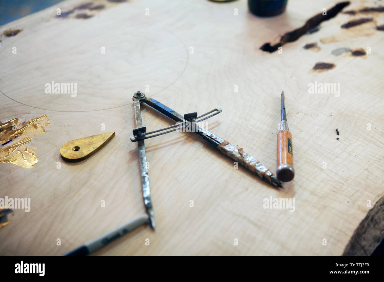 High angle view of drafting compass on wooden plank at workshop - Stock Image
