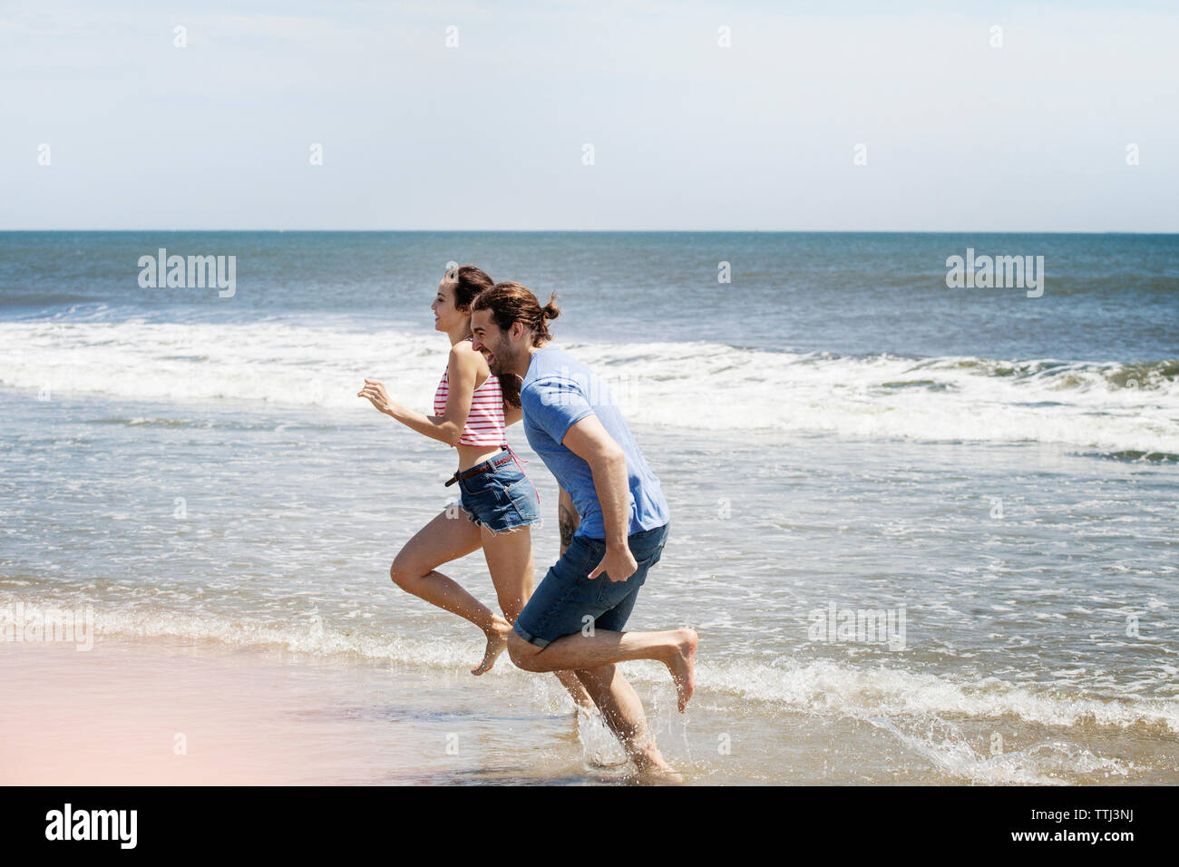 Side view of couple running on shore at beach during summer vacation - Stock Image
