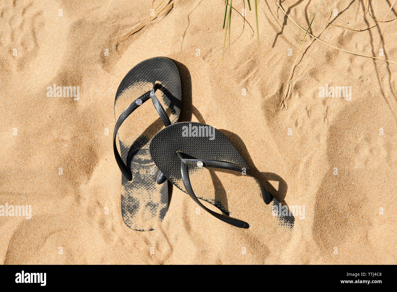Flip flop sandals in the sand - Stock Image