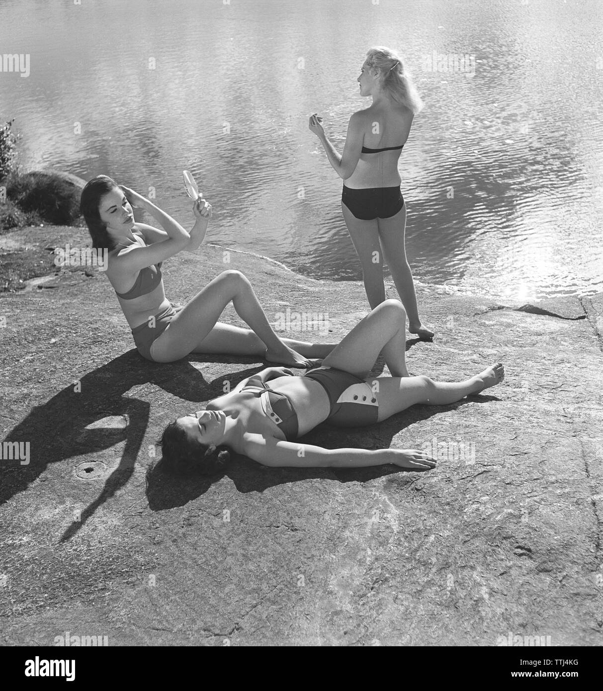 1950s summer. Three young women by the sea are getting a nice suntan. Sweden. Sweden 1955 Kristoffersson Ref BT2-2 - Stock Image