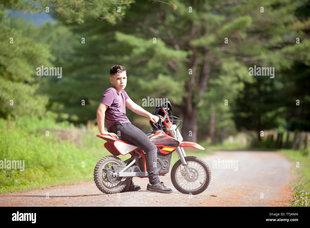 Portrait of boy sitting on dirt bike - Stock Image