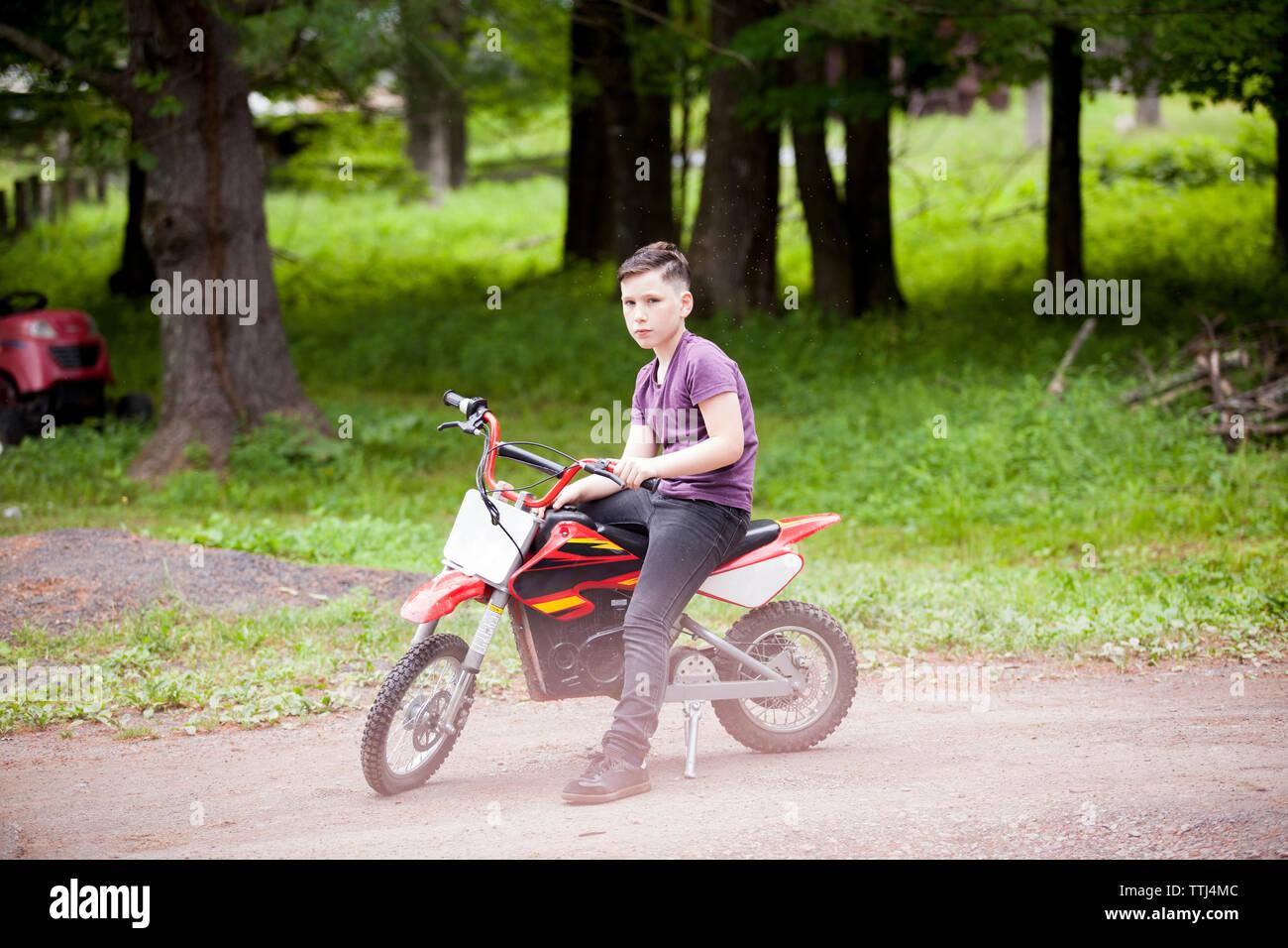Full length of boy sitting on dirt bike - Stock Image