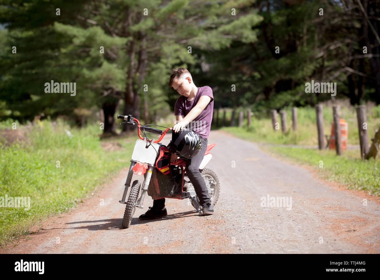 Boy holding crash helmet while sitting on dirt bike - Stock Image