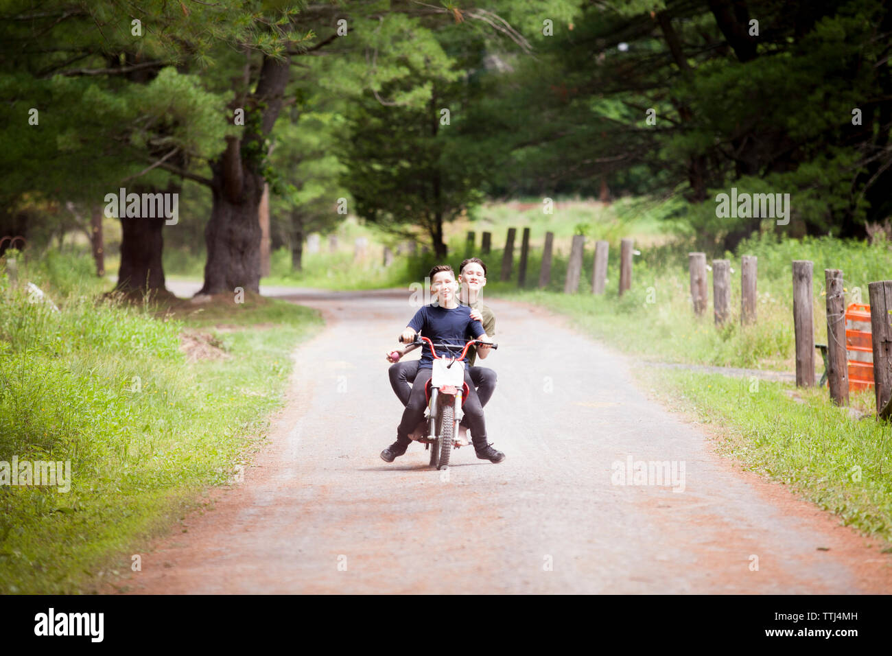 Brothers riding dirt bike on road - Stock Image