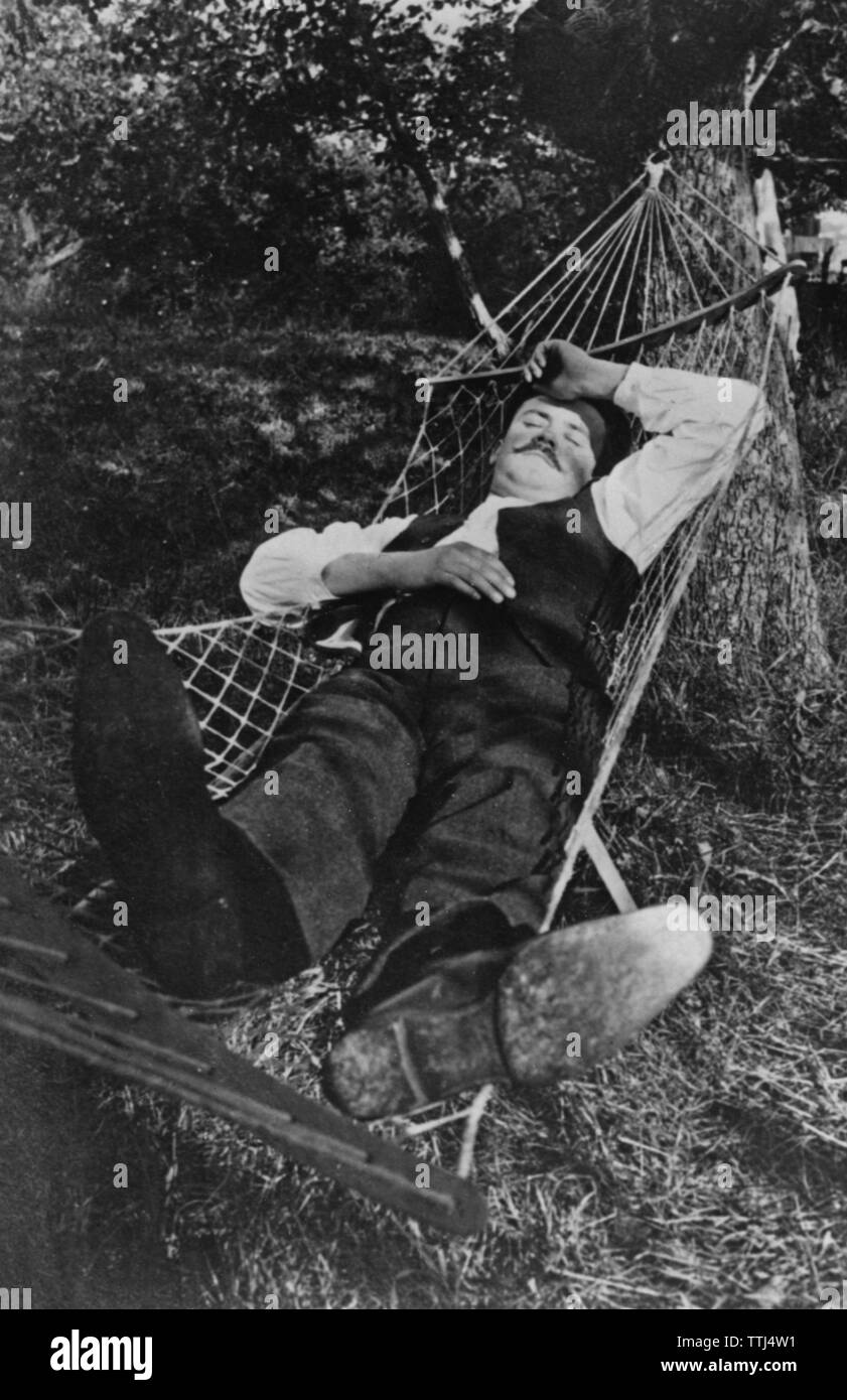 Summer in the 1940s. A man is lying comfortable in a hammock. - Stock Image