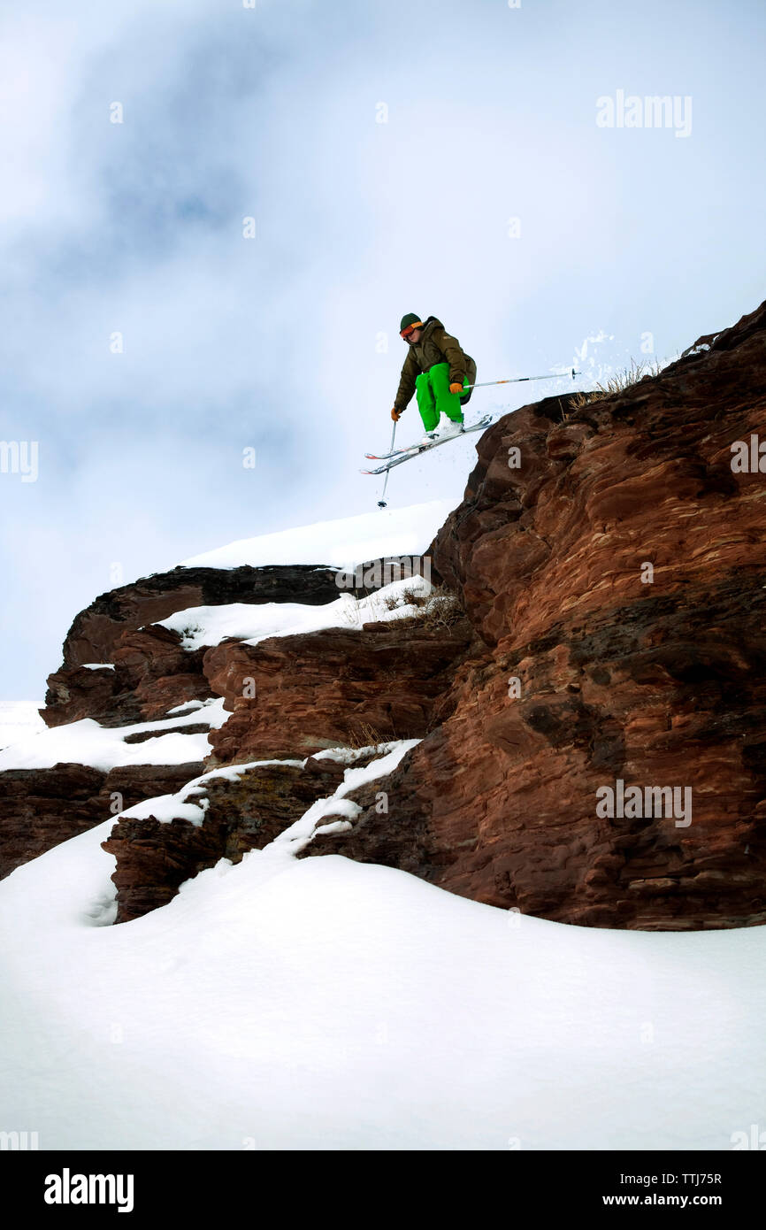 Male skier skiing downhill on mountain - Stock Image