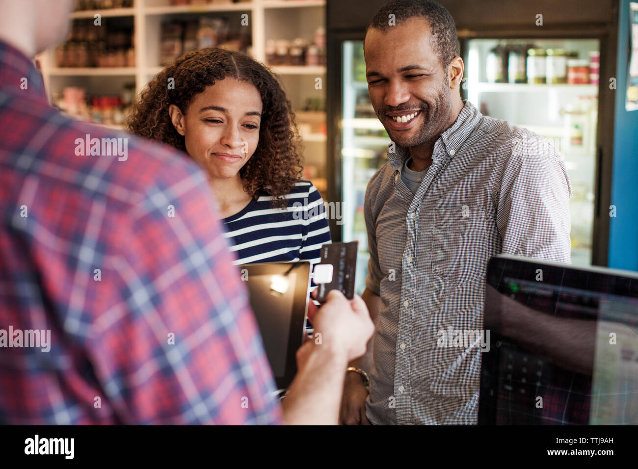 Happy couple looking at owner swiping credit card in store Stock Photo