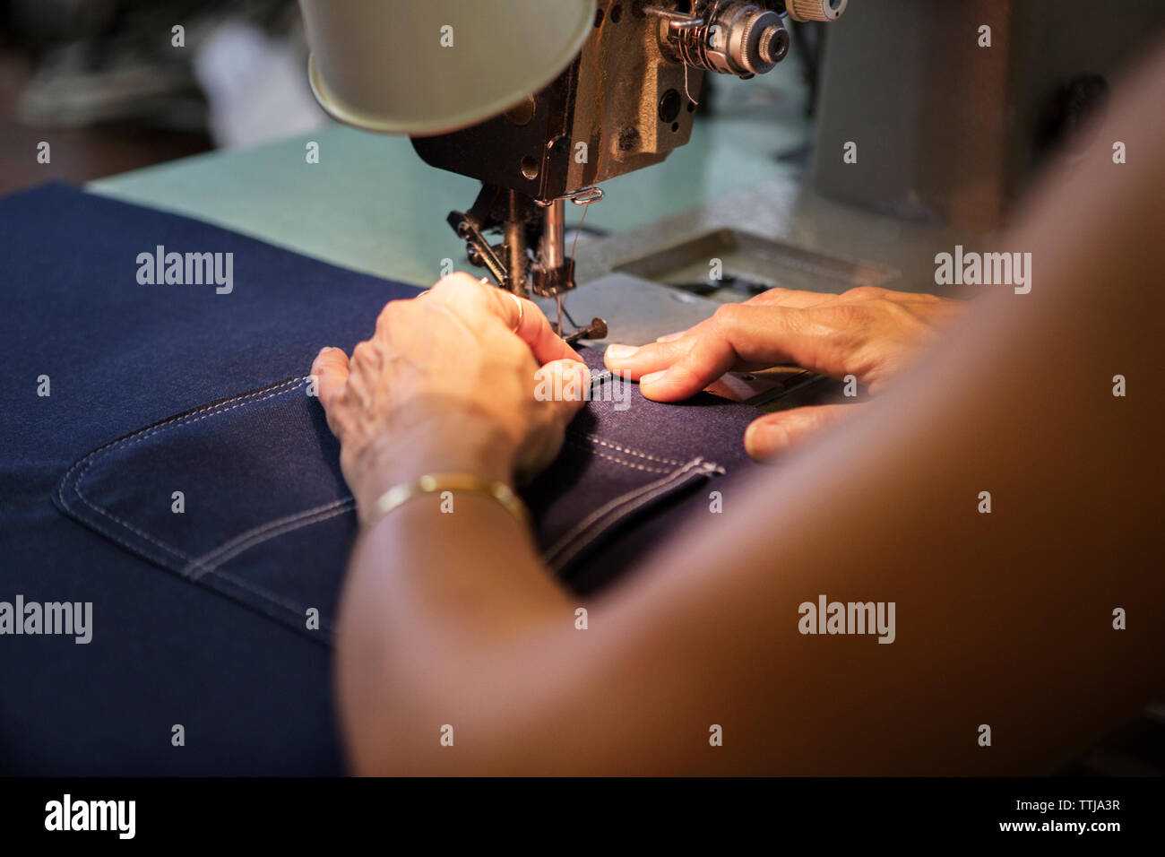 Close-up of woman sewing in textile factory - Stock Image