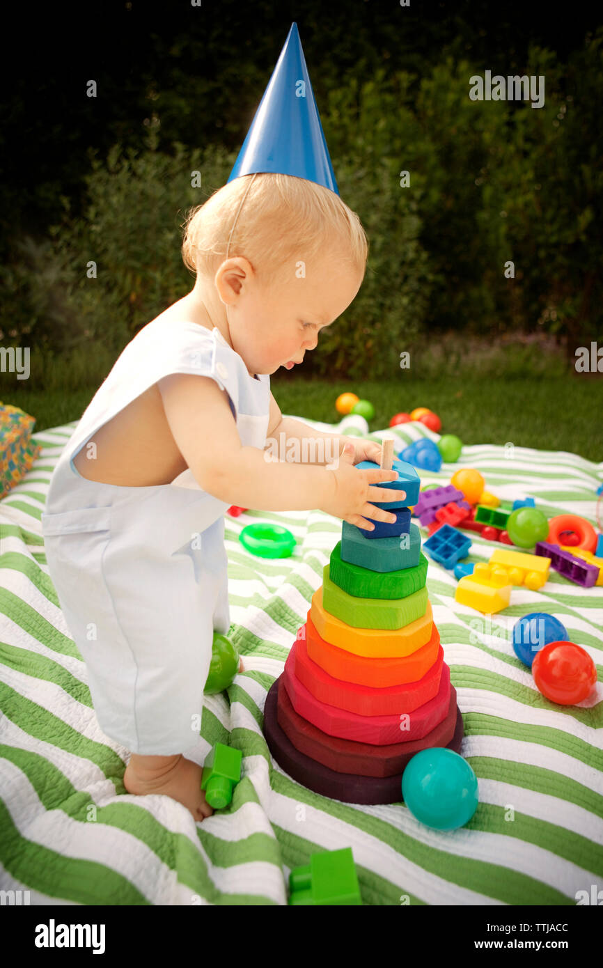 Side view of baby boy plying on picnic blanket in lawn - Stock Image