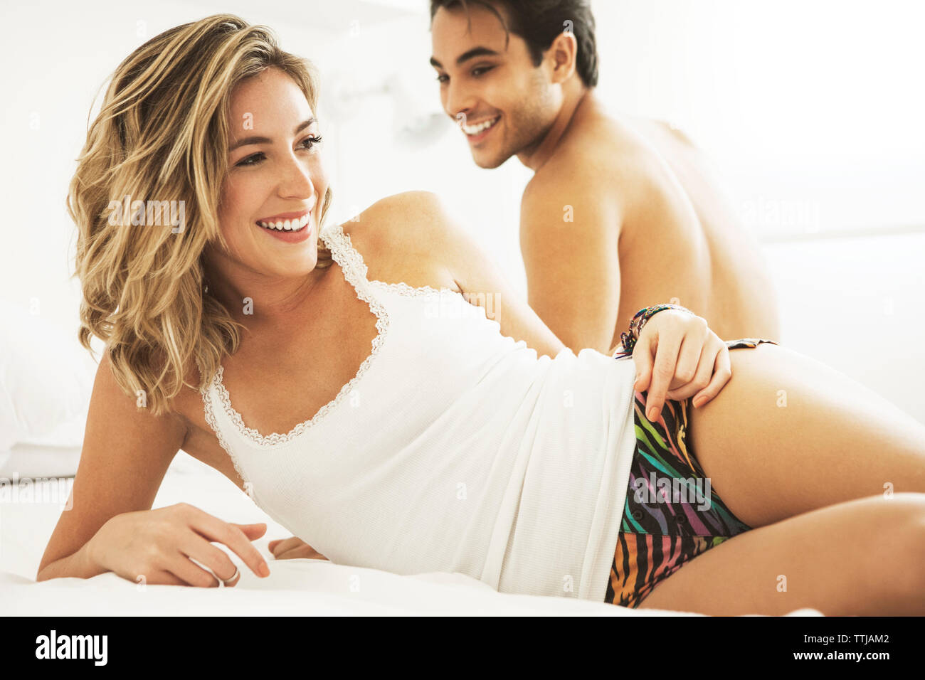 Happy couple relaxing on bed at home Stock Photo