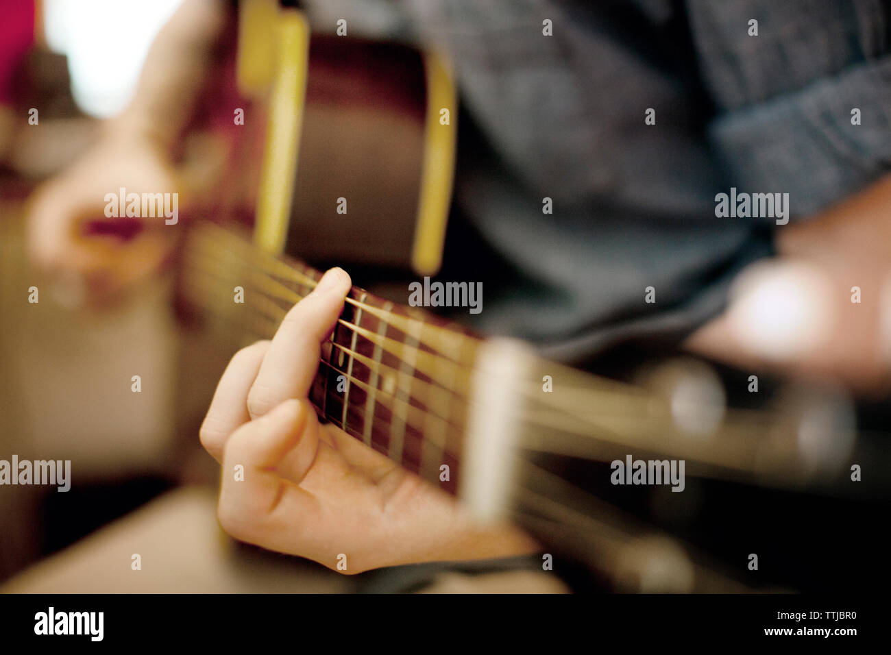 Midsection of man playing guitar - Stock Photo