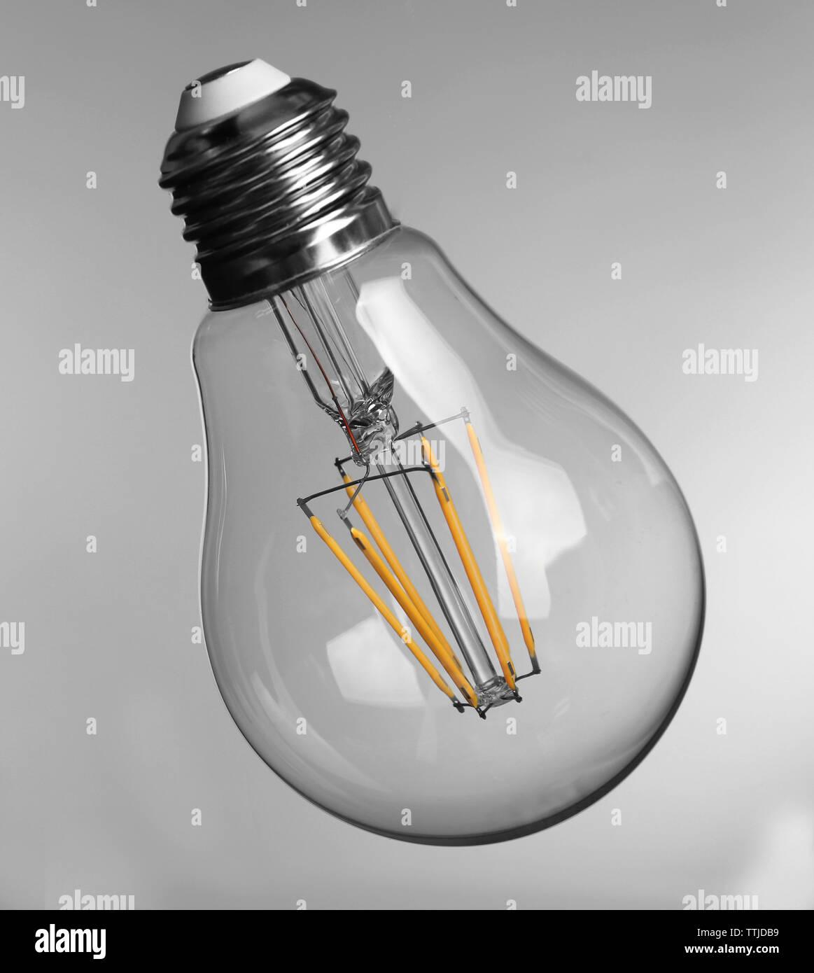 Light bulb on grey background - Stock Image
