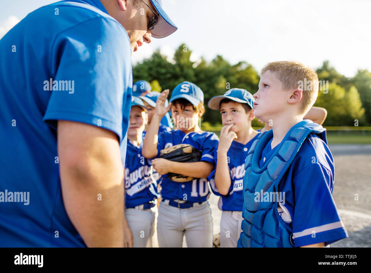 Coach guiding players on field - Stock Image