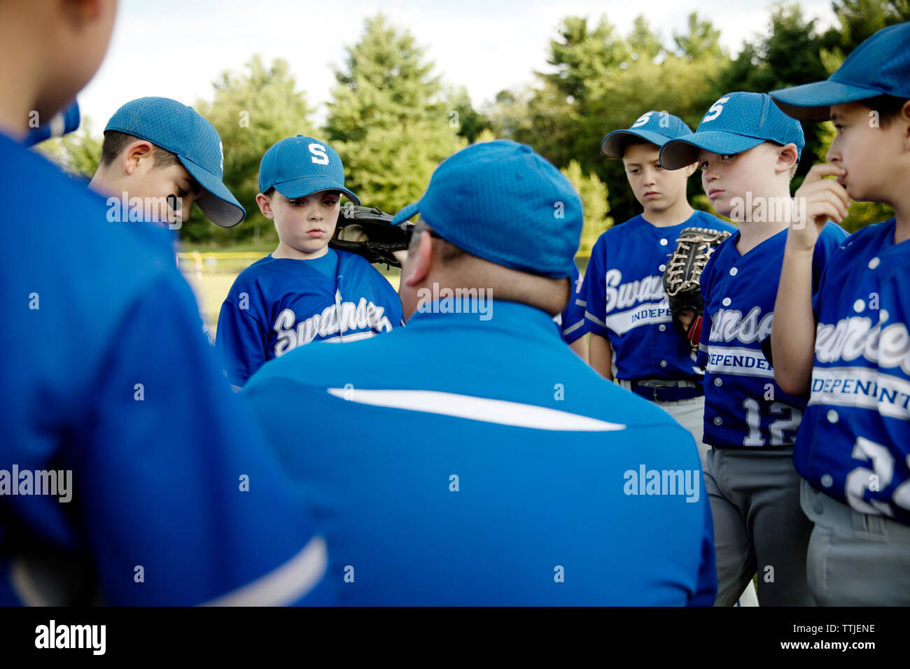 Coach guiding baseball players on field - Stock Image