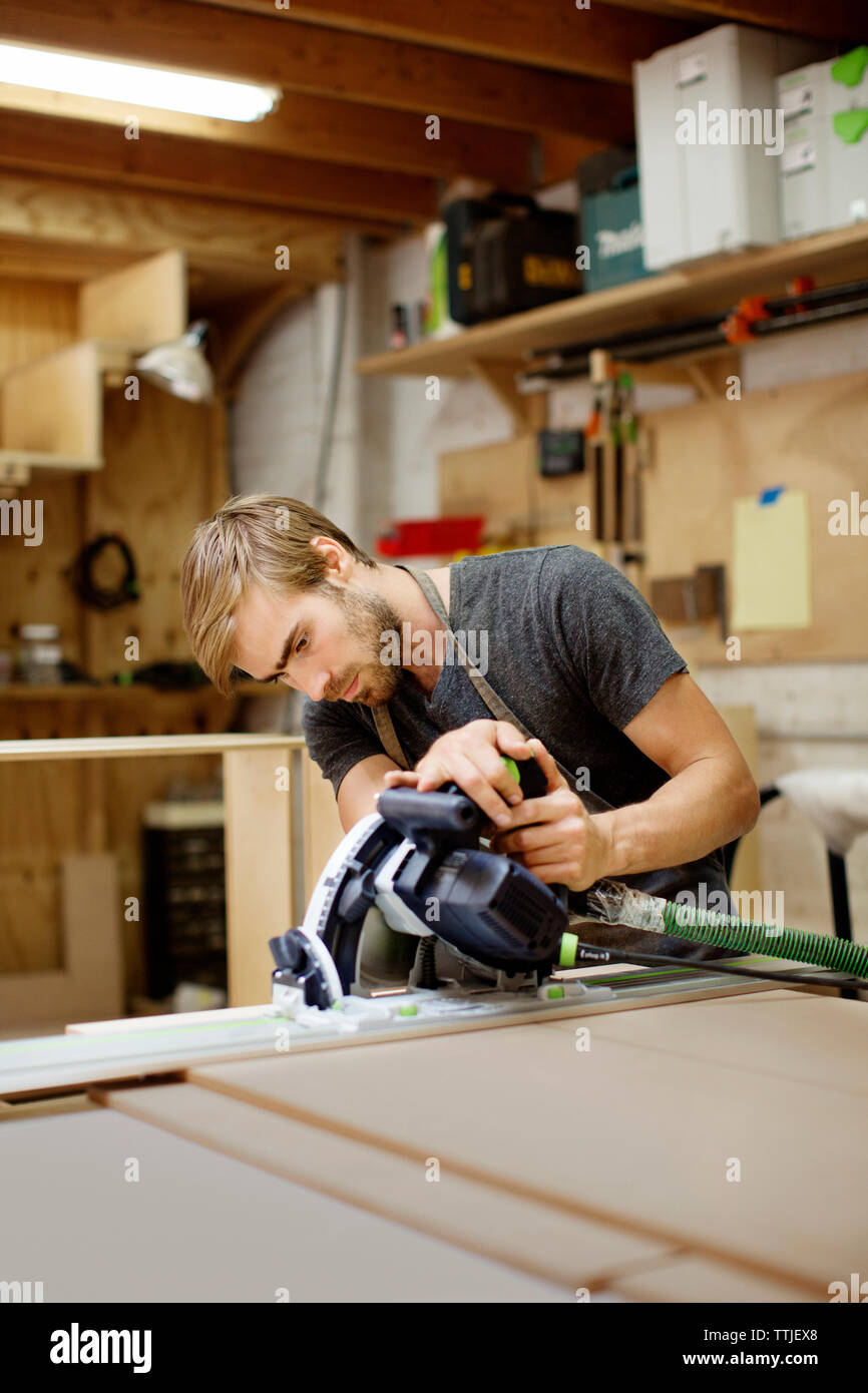 Worker working with power tool in carpentry workshop - Stock Image