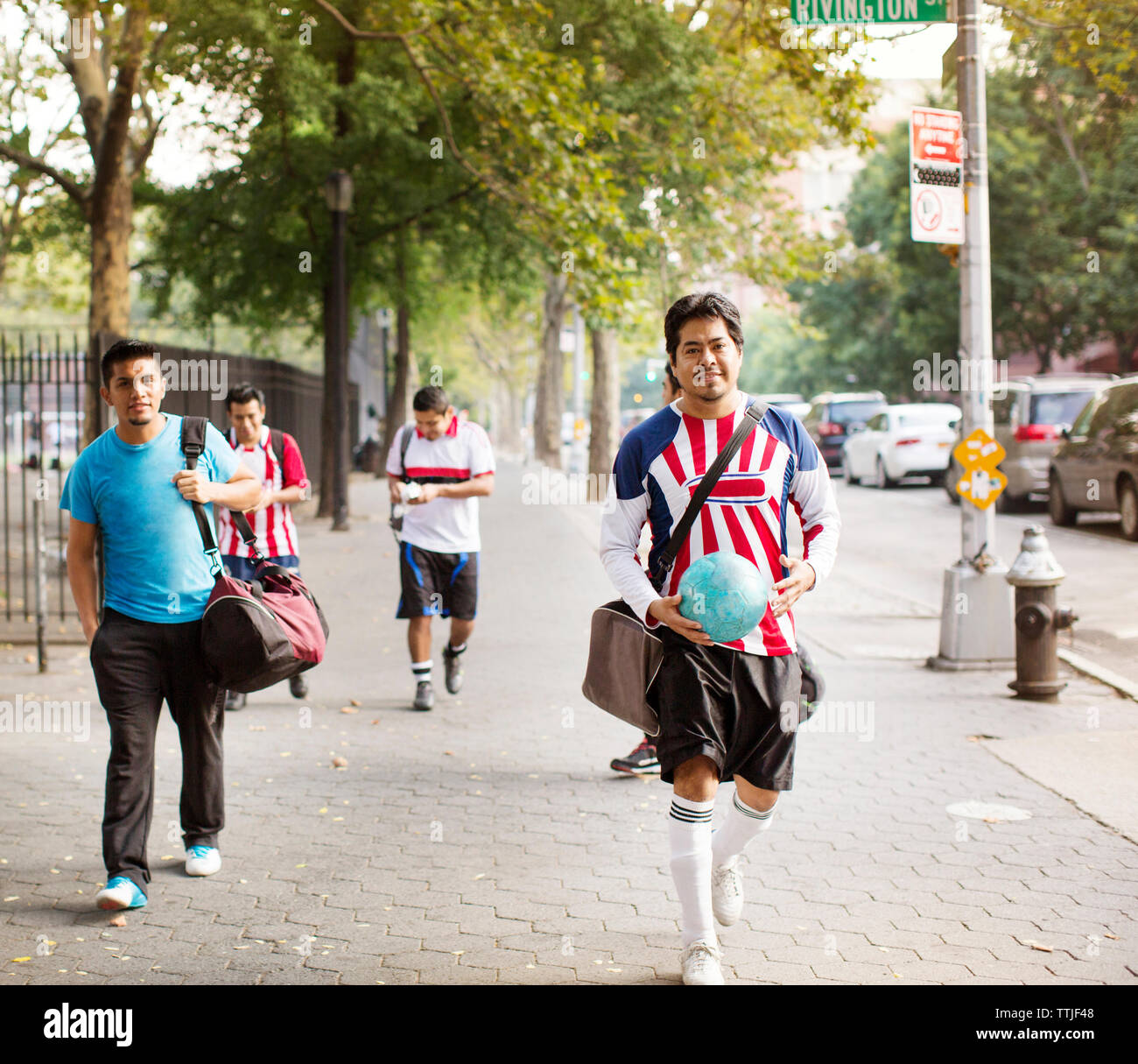 Portrait of soccer players walking on footpath - Stock Image