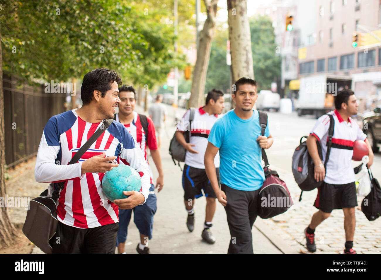 Happy soccer players walking on footpath - Stock Image