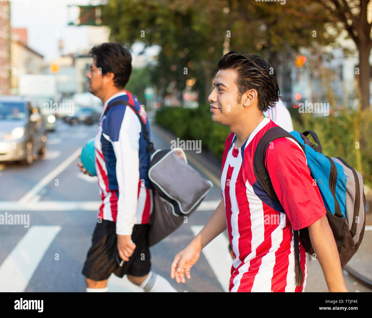 Soccer players crossing road at city street - Stock Image