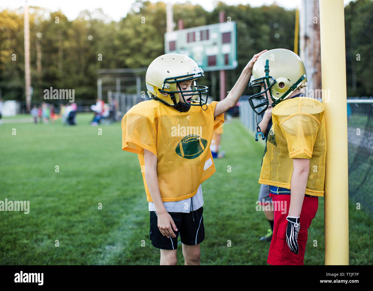 Side view of American football players on field - Stock Image