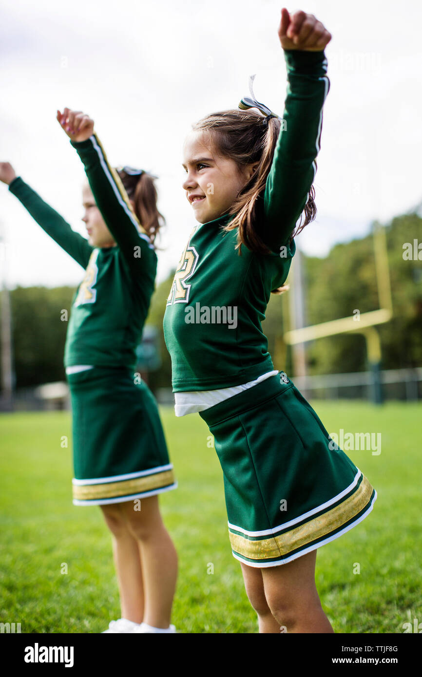 Happy cheerleaders dancing on field against sky - Stock Image