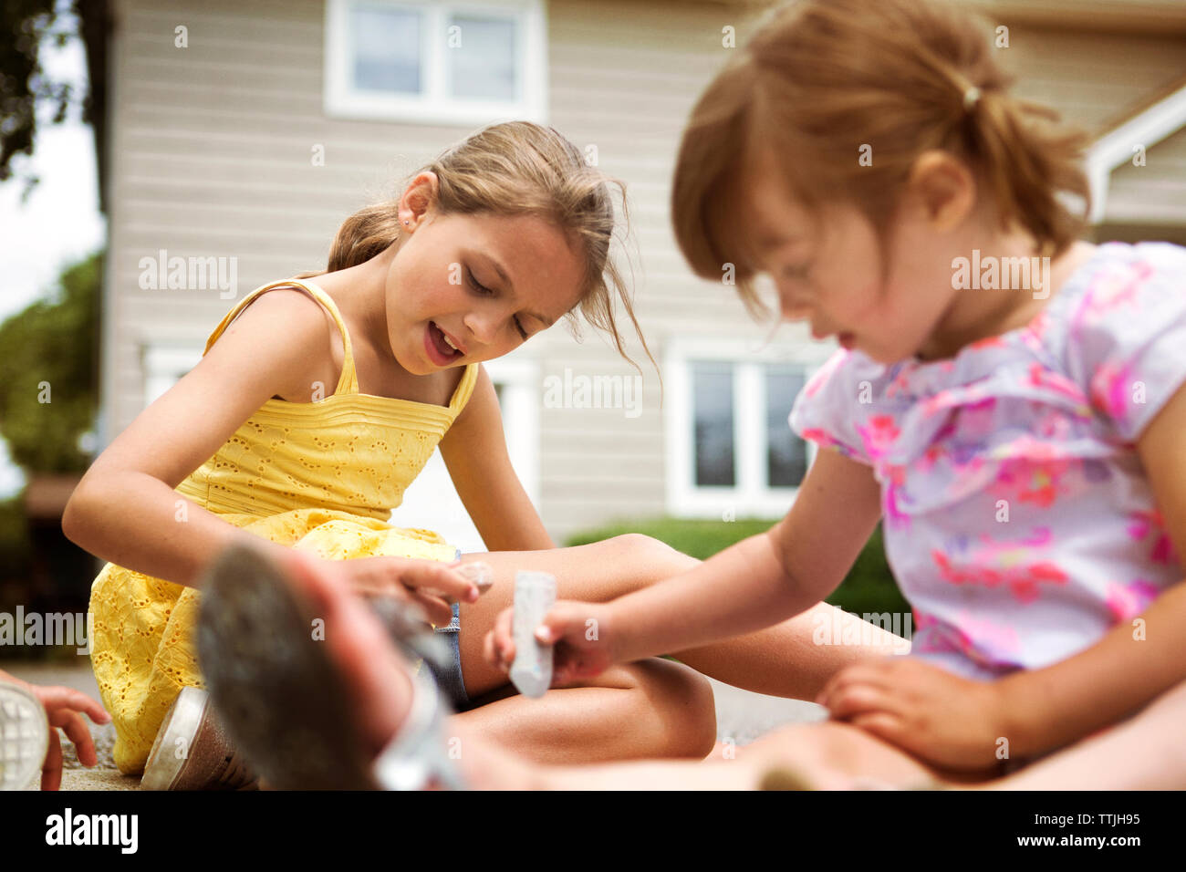 Girls doing chalk drawing on road Stock Photo