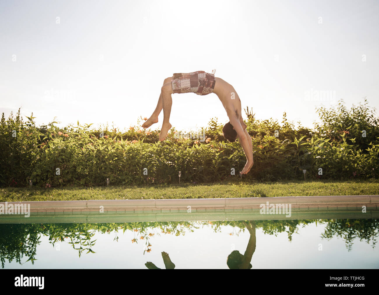 Man somersaulting into swimming pool against clear sky Stock Photo