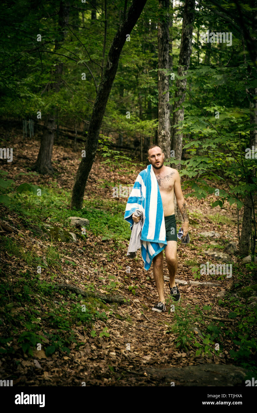 803093ab00 Shirtless man carrying towel and clothes while walking in forest - Stock  Image