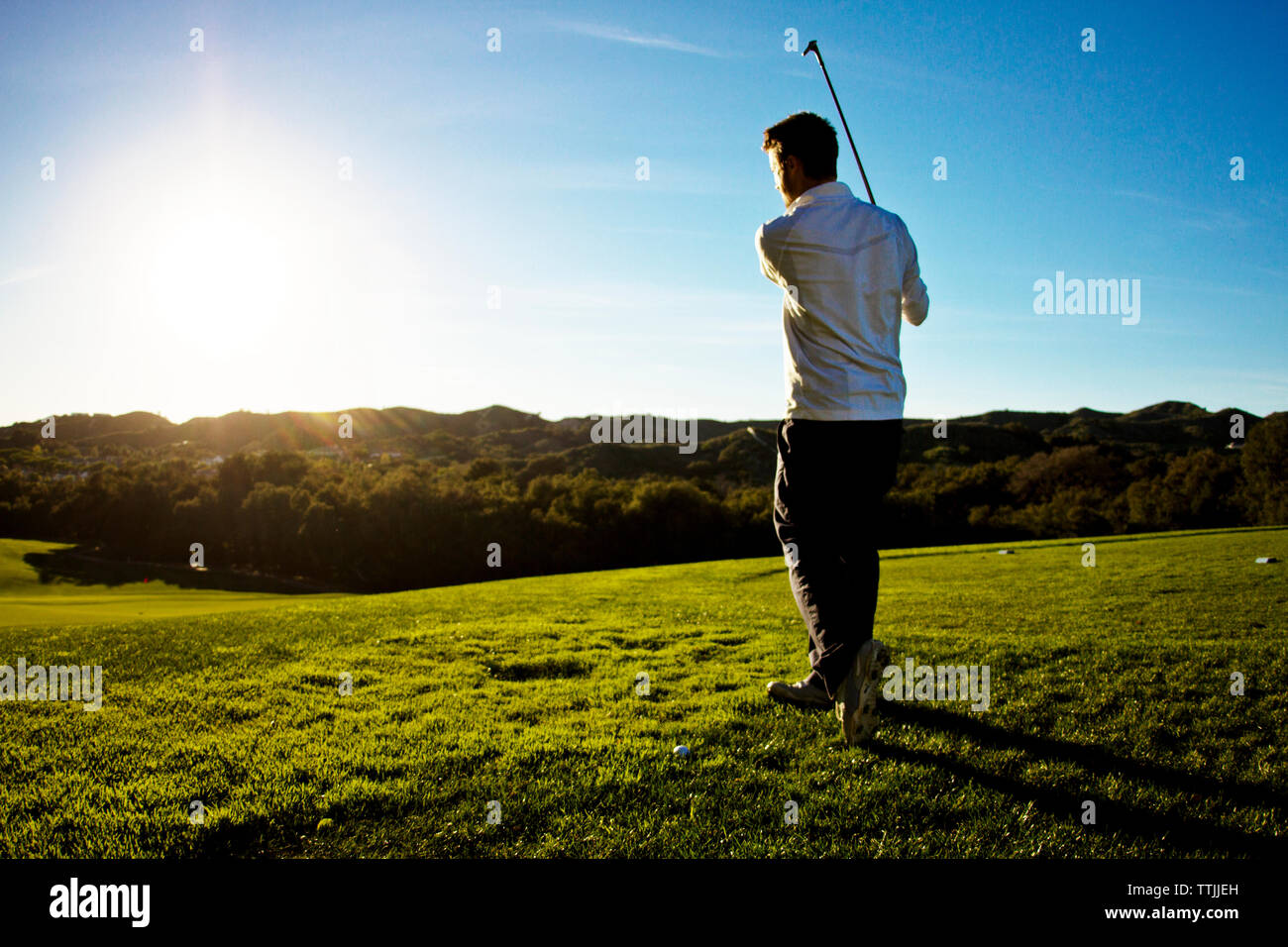 Rear view of man playing golf against clear sky Stock Photo