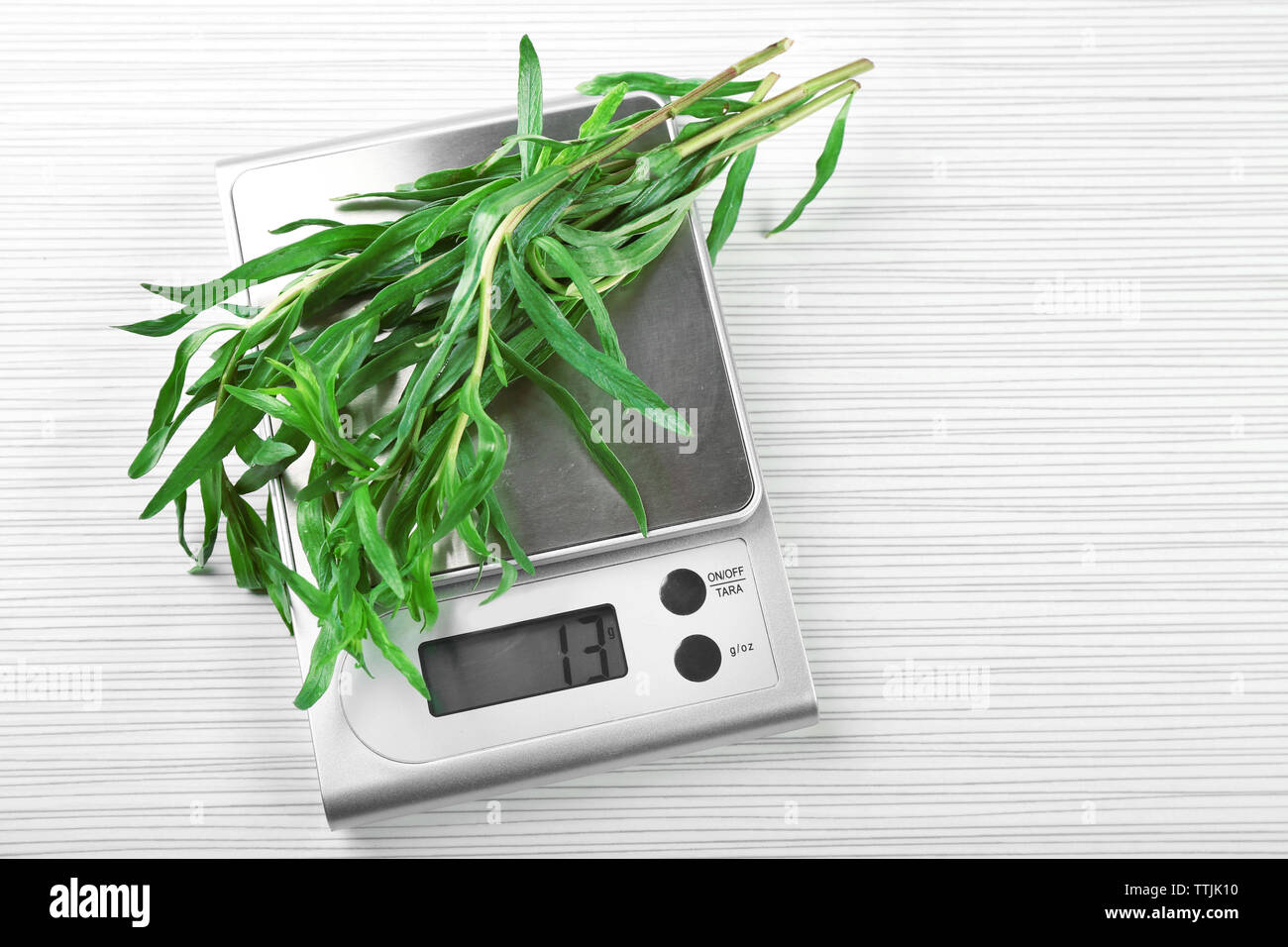 Herbs with digital kitchen scales on wooden background - Stock Image