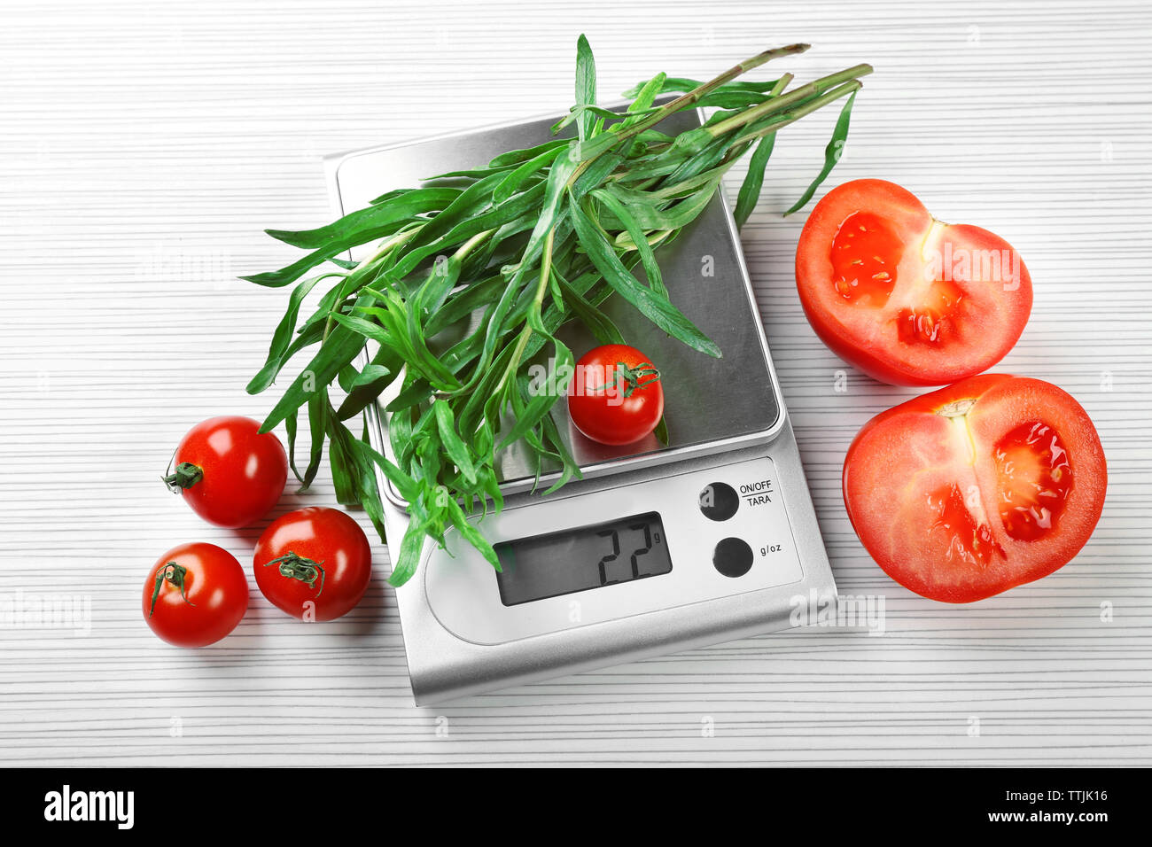 Tomatoes and tarragon with digital kitchen scales on wooden background - Stock Image