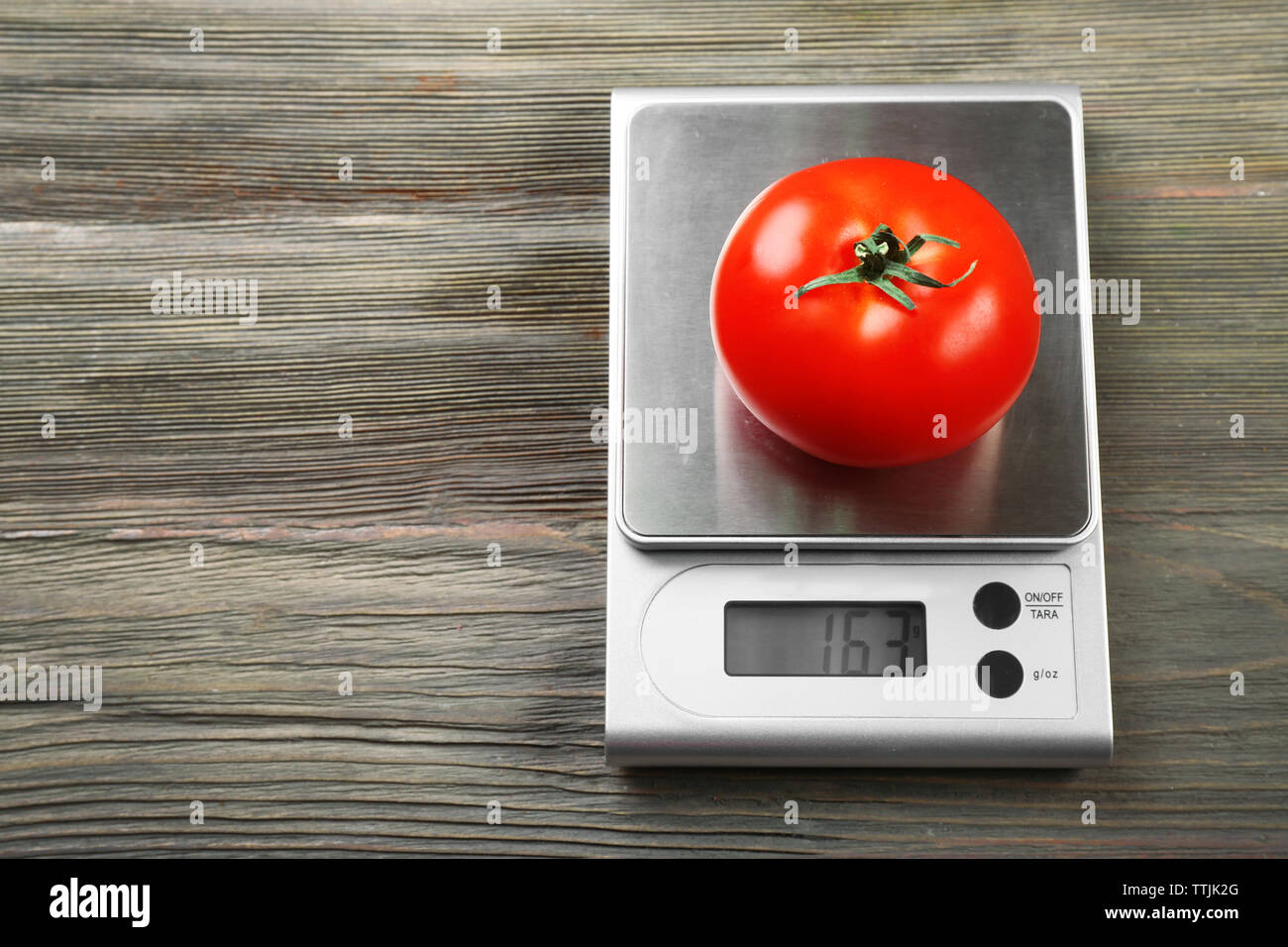 Tomato with digital kitchen scales on wooden background - Stock Image