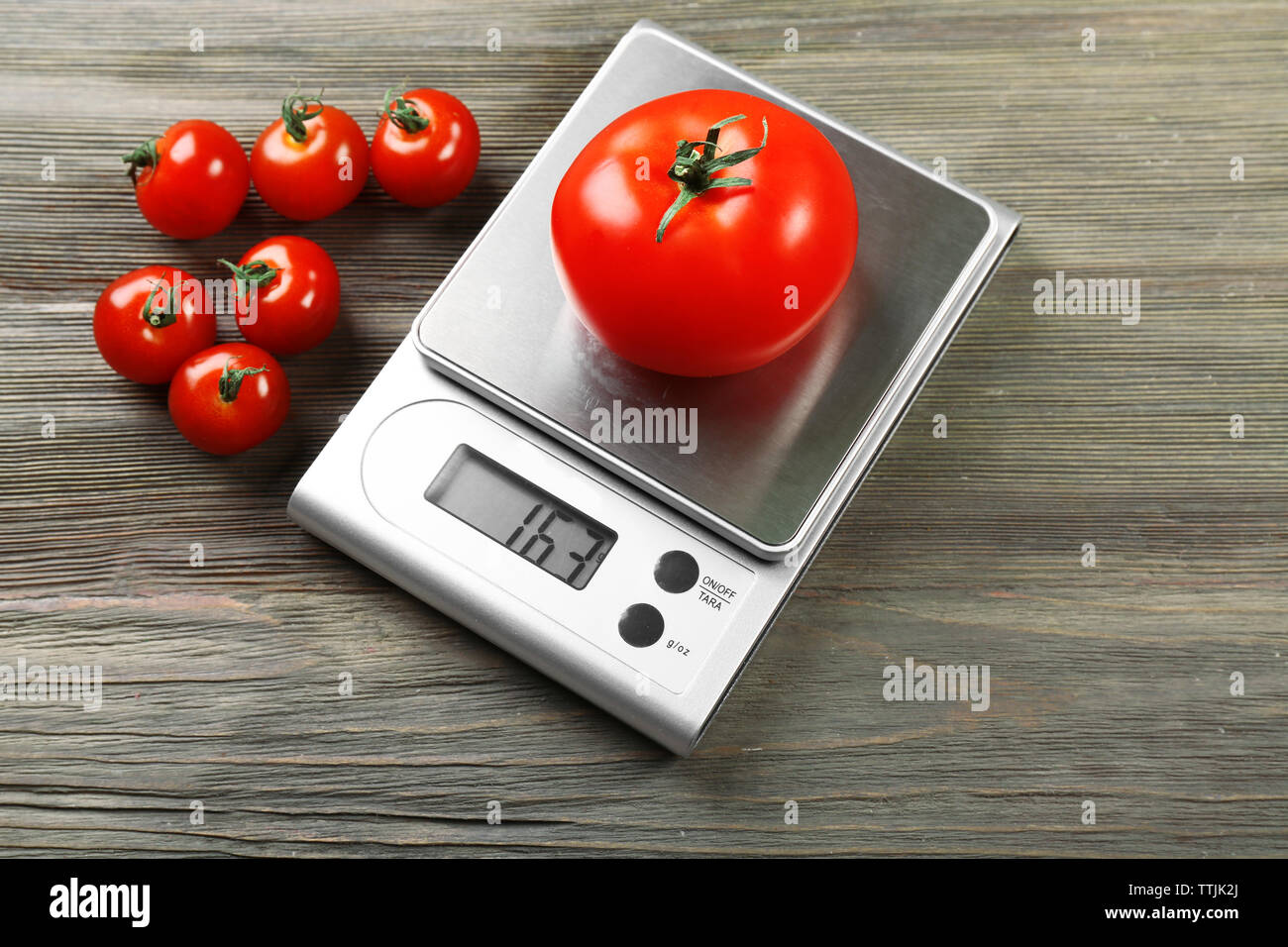 Tomatoes with digital kitchen scales on wooden background - Stock Image