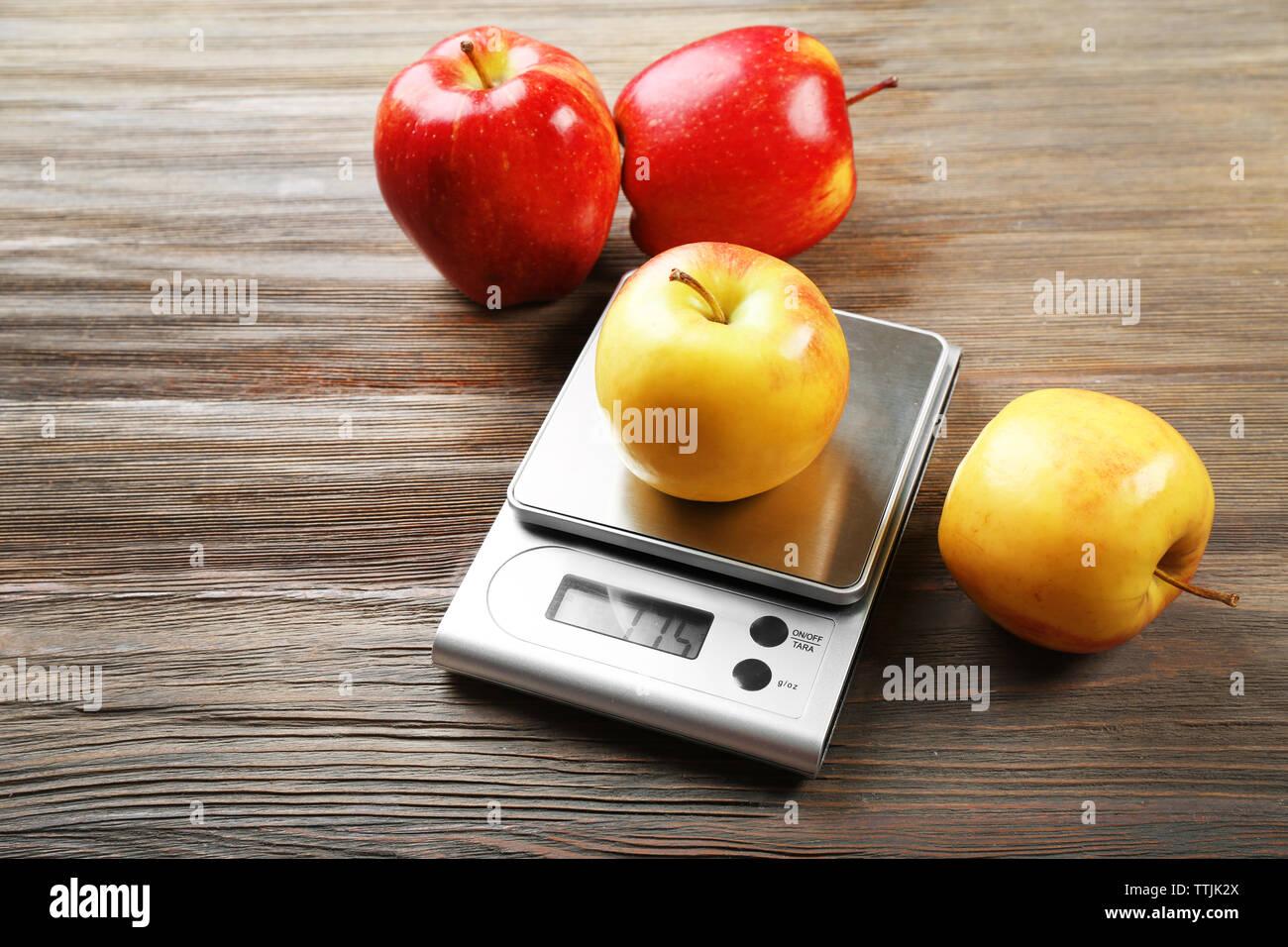 Apples with digital kitchen scales on wooden background - Stock Image