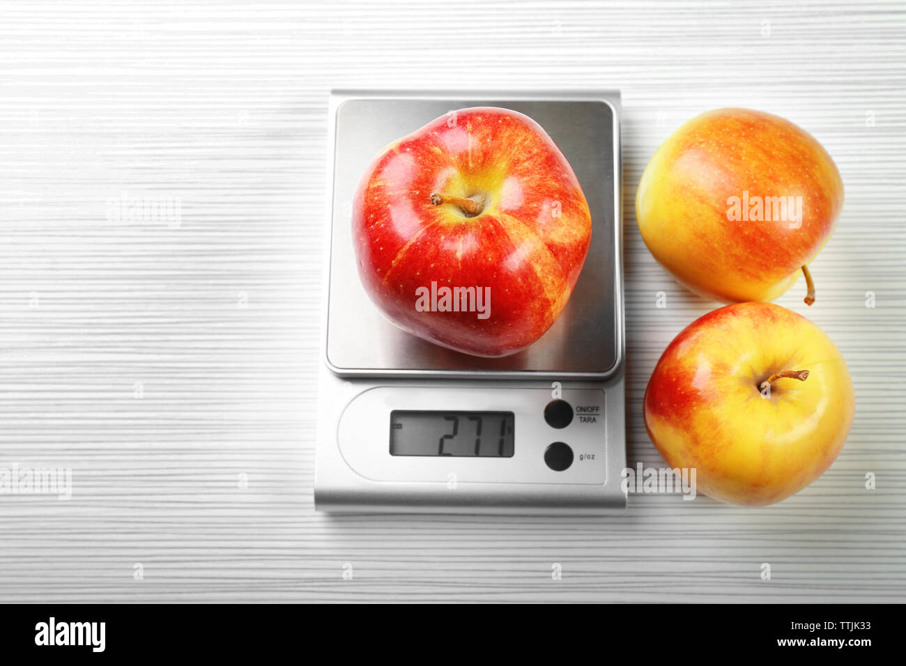 Apple with digital kitchen scales on wooden background - Stock Image