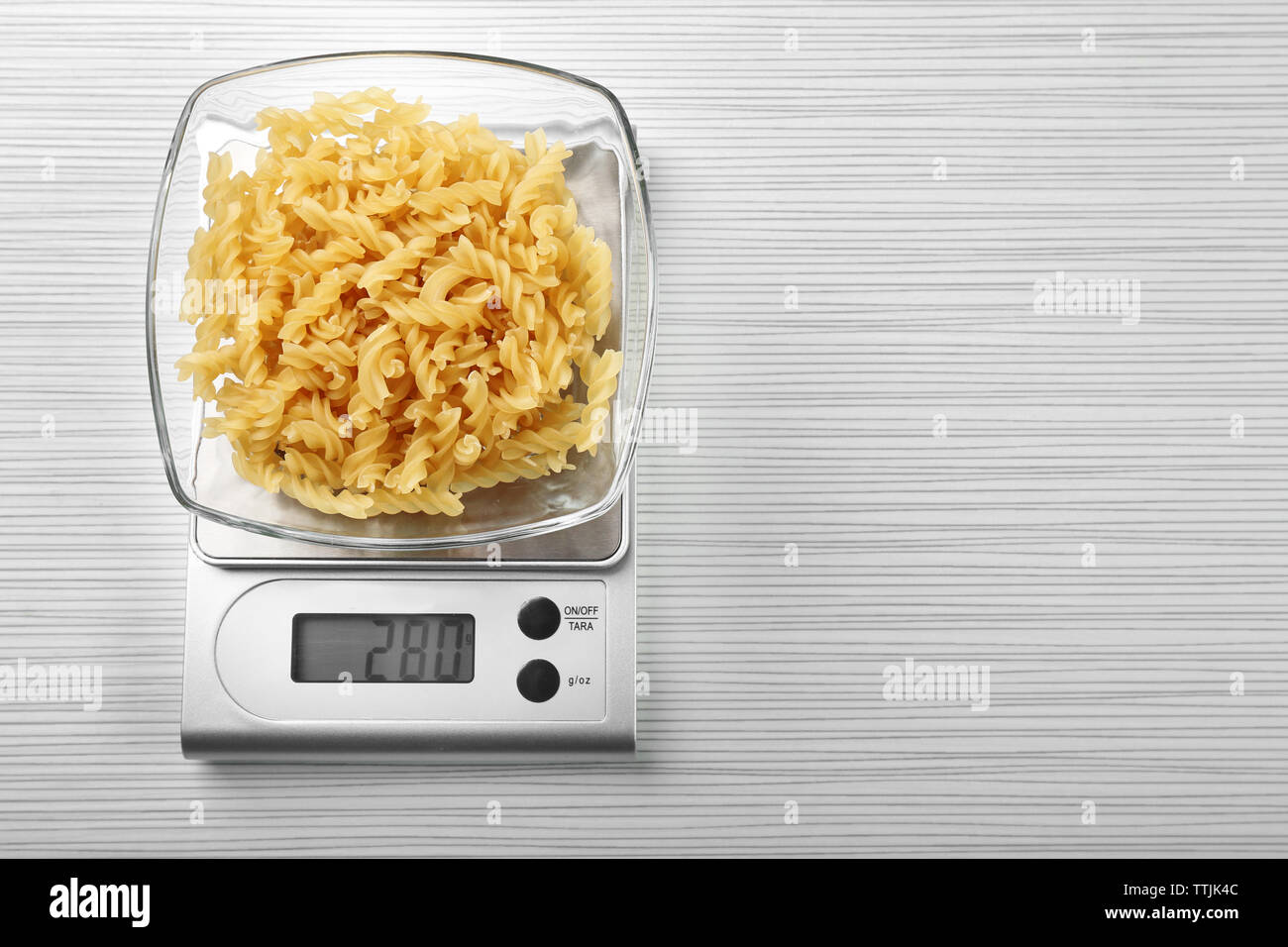 Pasta with digital kitchen scales on wooden background - Stock Image