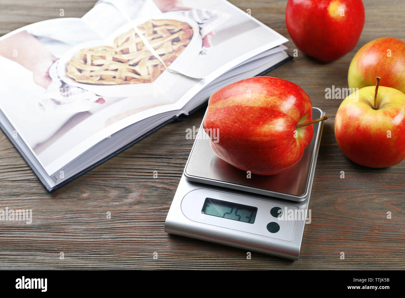 Apples with digital kitchen scales on wooden table. Cooking apple cake concept - Stock Image