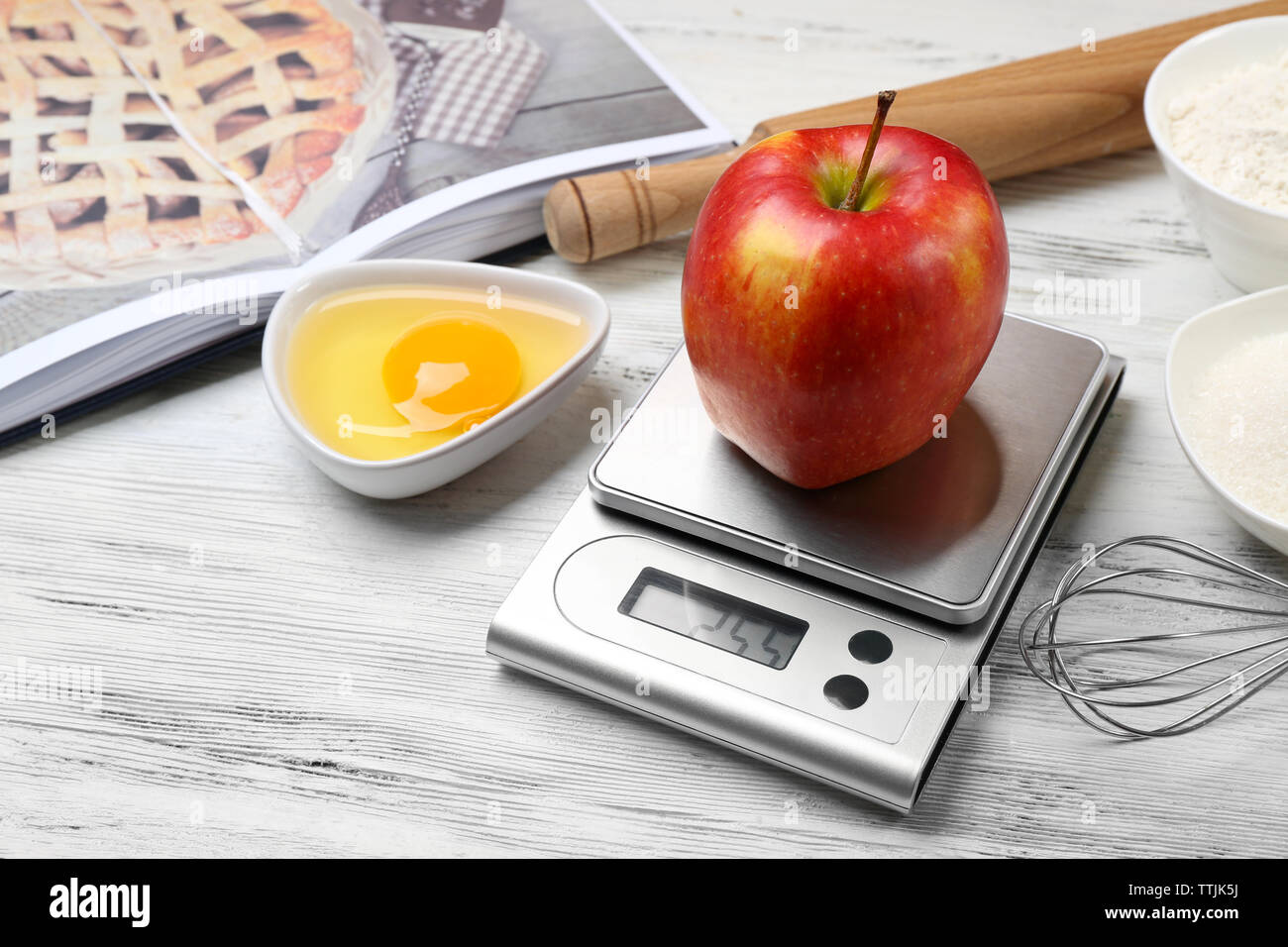 Apple with digital kitchen scales on wooden table. Cooking apple cake concept - Stock Image