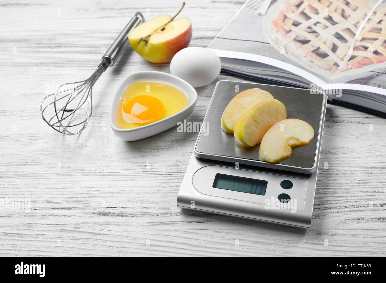 Making apple pie. Using digital kitchen scales on wooden table. Cooking apple cake concept - Stock Image