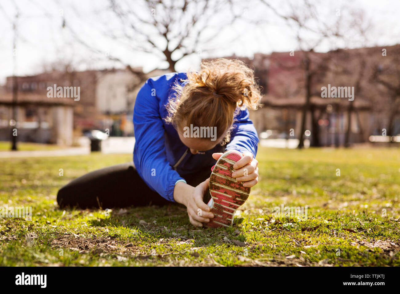 Woman exercising while sitting on field in park - Stock Image