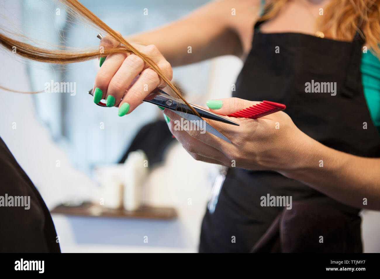 Midsection of hairstylist cutting woman's hair in salon - Stock Image