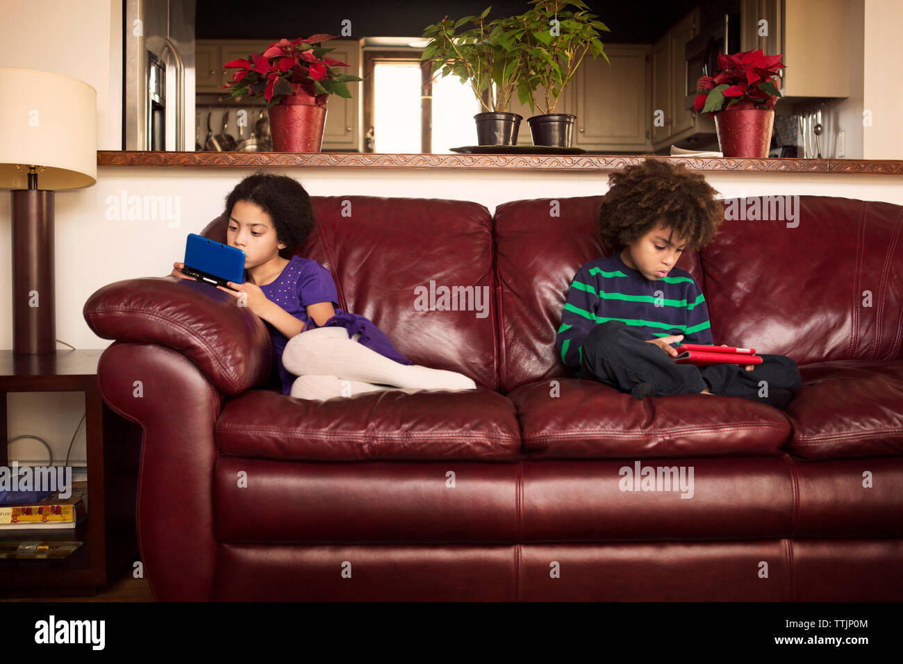 Brother and sister using technologies while sitting on leather sofa at home - Stock Image
